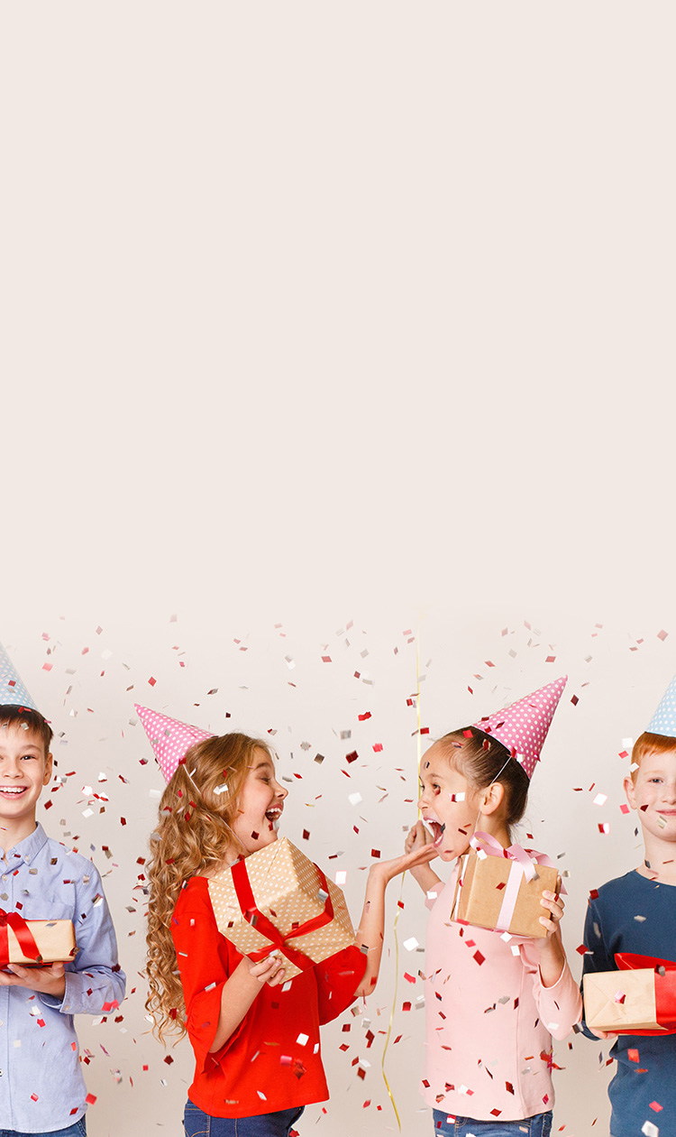 Kids celebrating birthday holding balloons and presents wearing birthday hats with confetti falling over white background