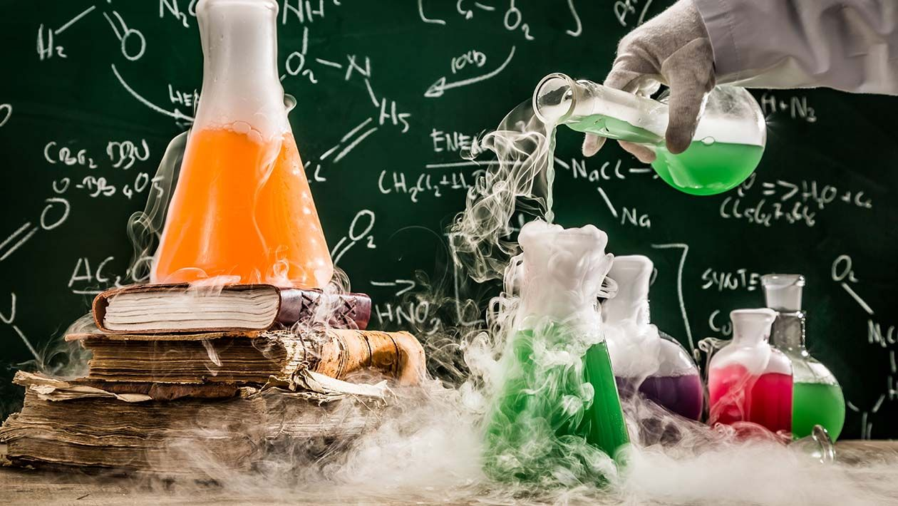 Hand pouring liquid into beaker on a desk.  Another beaker on a stack of books with smoke surrounding all beakers and table
