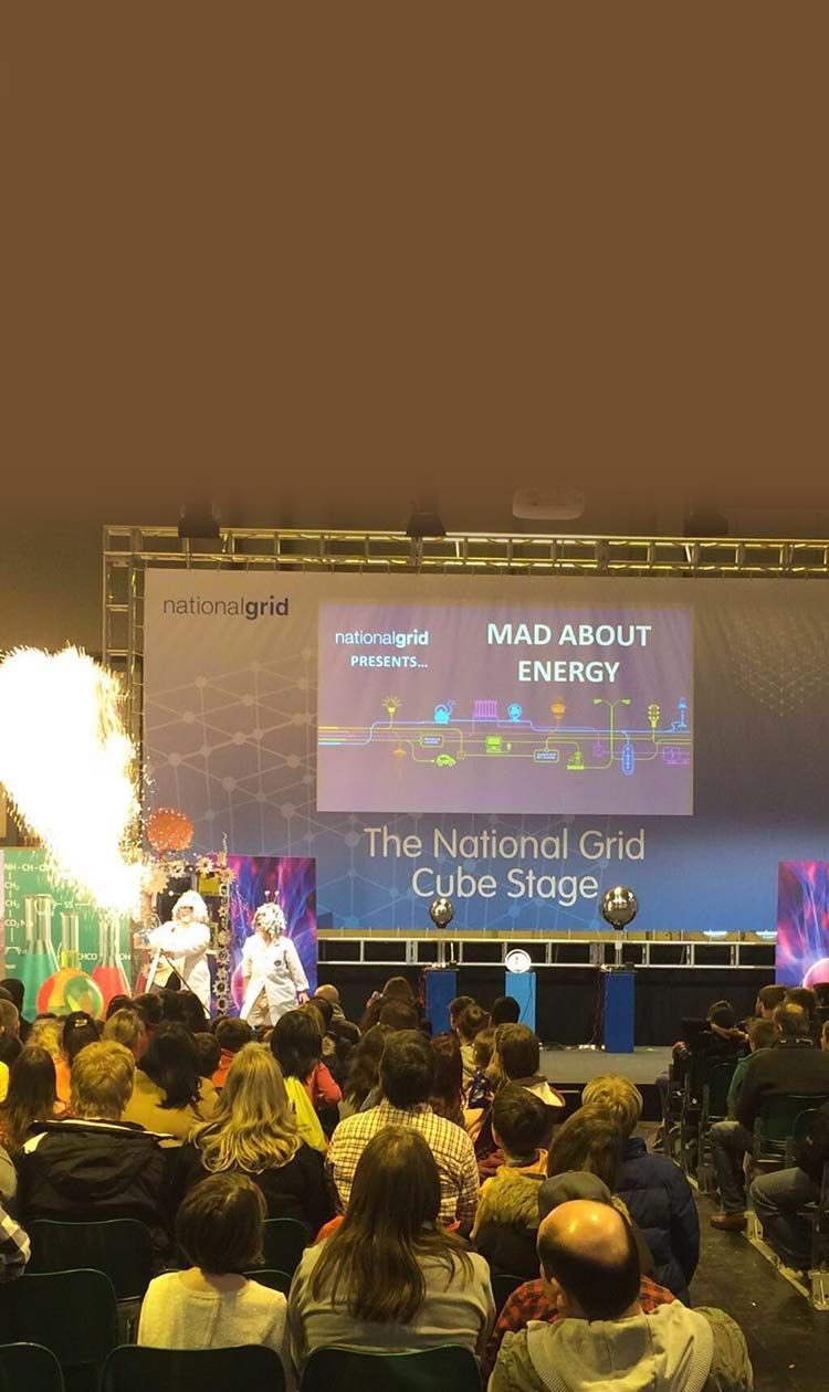 Mad Scientist blowing fire out of machine while kids look on at a mad science special event
