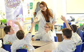 Mad Scientist passing stack of activity cups to student while kids in classroom look on